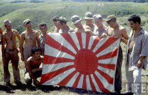 American soldiers display captured Japanese flag on Guadalcanal